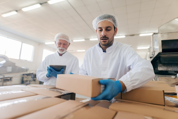 Man stacking boxes while other man standing and using tablet. food factory interior.