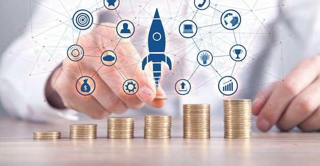 コインとロケットを積み重ねる男。成長の概念。投資。成功