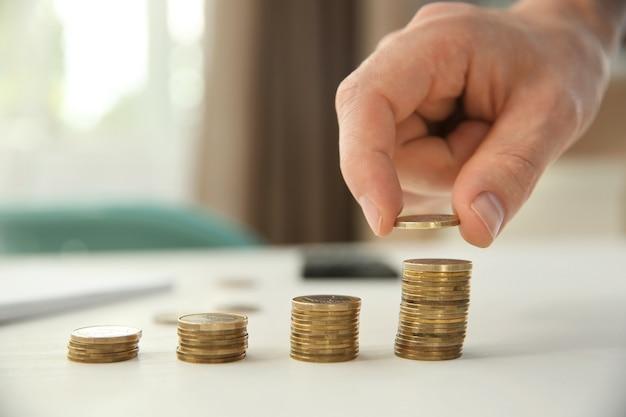 Человек, укладывая монеты на столе, крупным планом. концепция сбережений