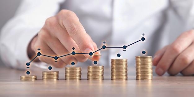 利益のグラフでコインを積み重ねる男。