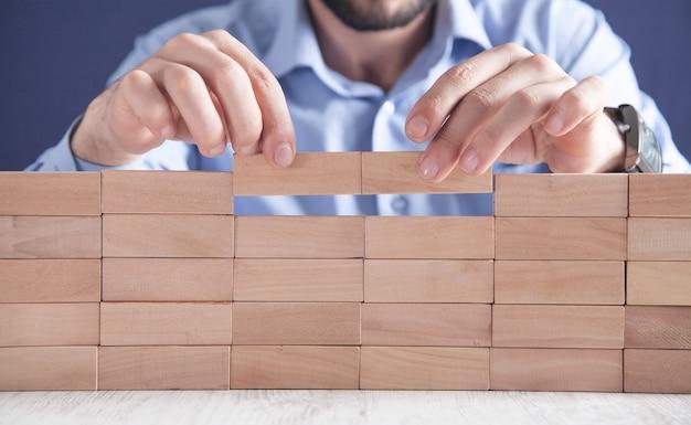 木製のブロックを積み重ねる男。開発コンセプト