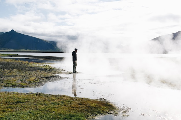 Man stand over geyser lake in iceland