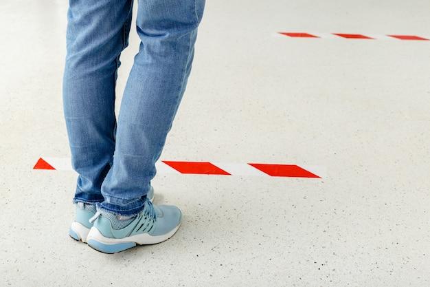 남자는 사회적 거리를 유지하면서 줄을 서고, 사람들은 코로나 19 격리 기간 동안 경고 선 뒤에 서 있습니다.
