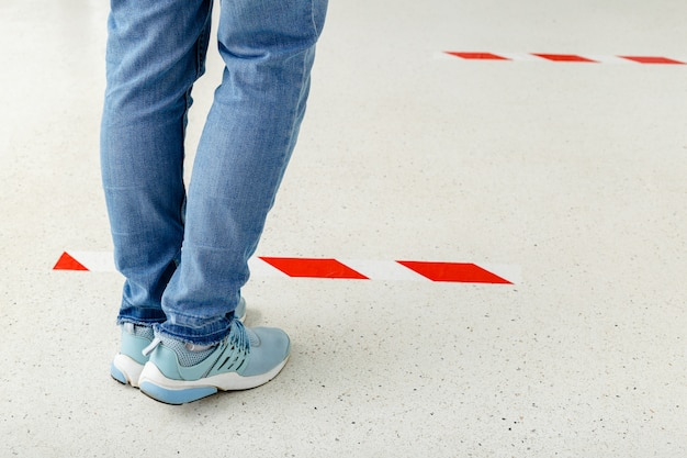 Man stand in line keeping social distance, people standing behind a warning line during covid 19 coronavirus quarantine.