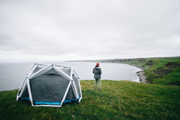 Man stand next to modern tent in iceland