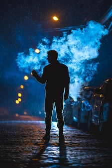 The man stand near the cloud of smoke. evening night time