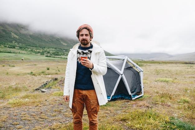 男はアイスランドのモダンなテントの隣に立つ