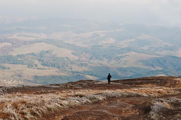 Человек стоять на холме и глядя на горы.