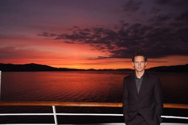 Человек стоит на палубе корабля на драматическом небе над морем в бергене, норвегия. бизнесмен наслаждается морским путешествием в вечернее время. деловая или прогулочная поездка. летний отдых на море. приключения и страсть к путешествиям. закат или восход солнца.