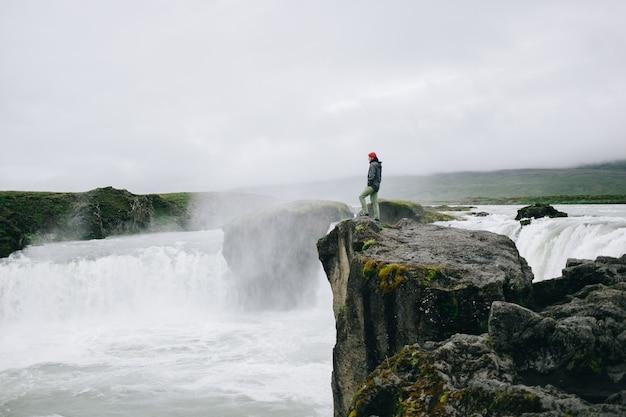 男は壮大な滝の崖の上に立つ