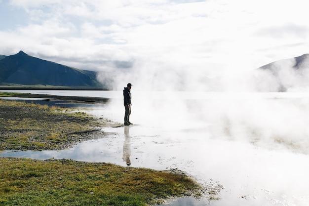 男はアイスランドの間欠泉湖の上に立つ