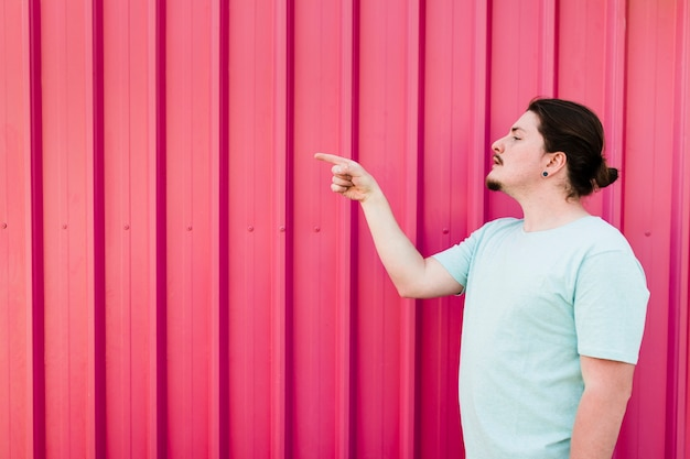 Man standing against red shutter pointing finger to side
