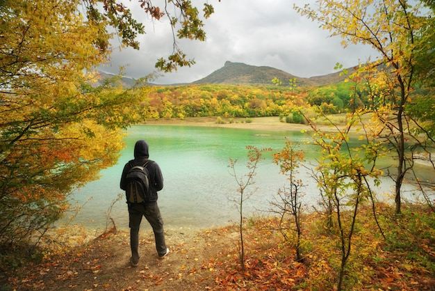 Man standing alone on the autumn pond