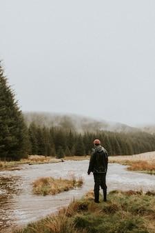 雨天の水辺に一人で立っている男