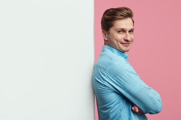 Человек, стоящий рядом с пустой белой стеной рекламного щита и улыбающийся
