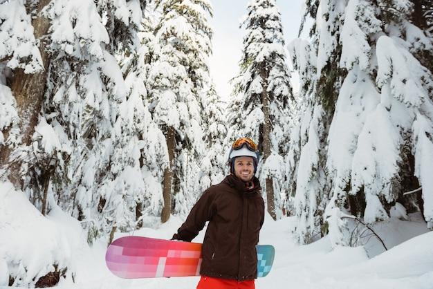 立ってスノーボードを持っている男