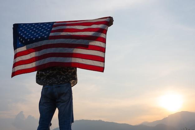 日の出ビューで米国旗を立って保持している男