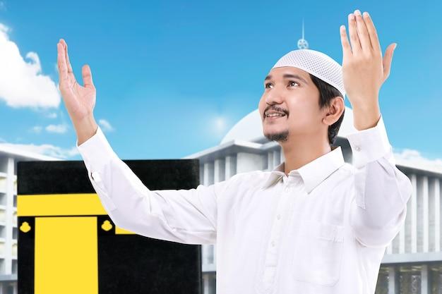 Человек, стоящий и молящийся с видом на каабу и фоном голубого неба