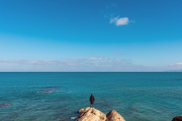 穏やかな海を見ながら、海岸に立っている男。