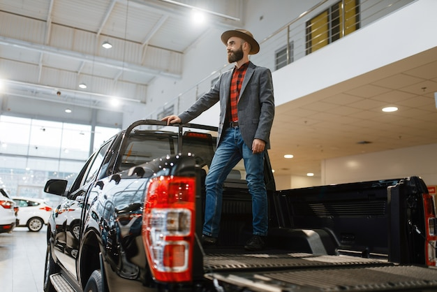 Man standing in the back of new pickup truck in car dealership. customer in vehicle showroom, male person buying transport, auto dealer business