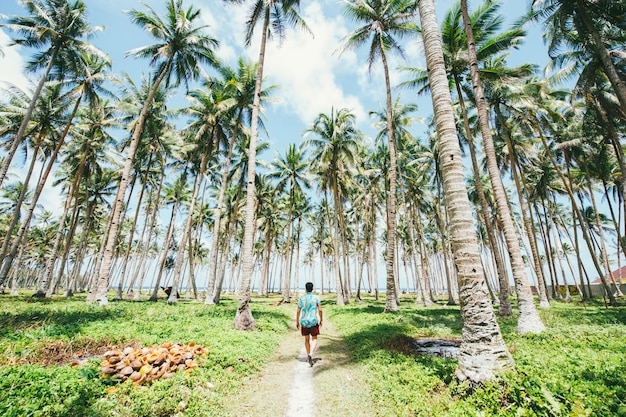 Man standing on the beach and enjoying the tropical place with a view. caribbean sea colors and palm trees in the background. concept about travels and lifestyle