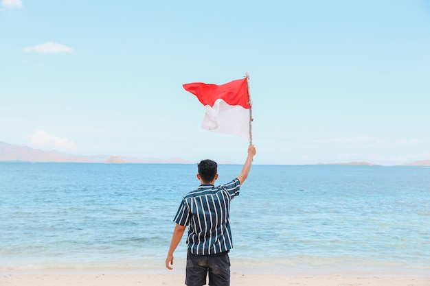 A man standing in the beach and waving indonesian flag with seascape background