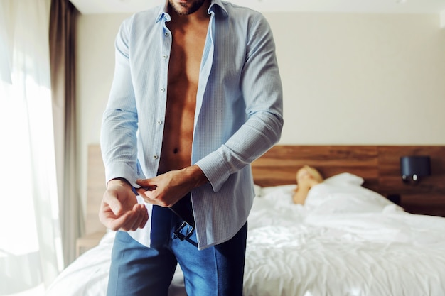 Man standing next to a bed in a hotel room and buttoning up a shirt.