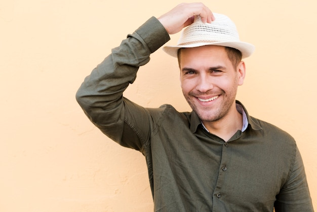 Man standing over beige background holding hat and smiling