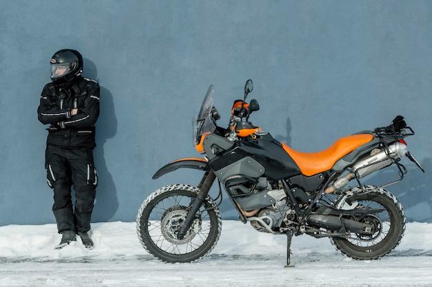 헬멧 오토바이 옆에 서있는 남자