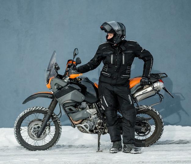 ヘルメットとオートバイの横に立っている男