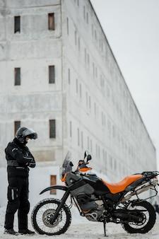 Man standing beside motorcycle with helmet