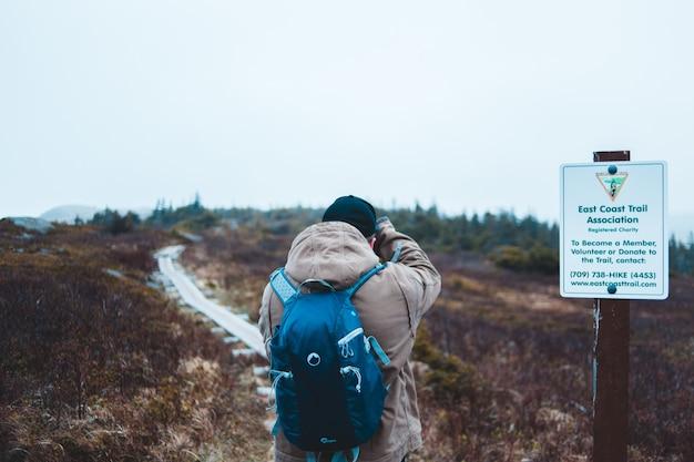 オープンフィールドの道路標識の横に立っている人