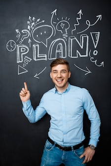 Man standing over blackboard with a plan concept point above