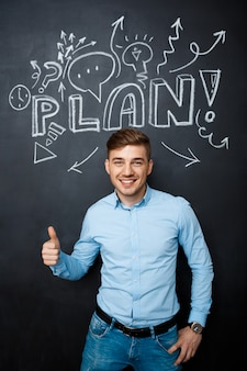 Man standing over blackboard with a plan concept thumbs up