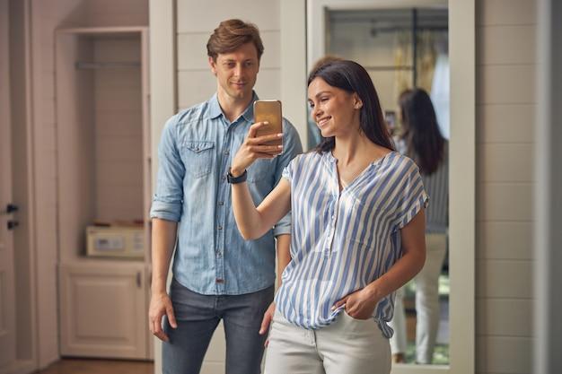 그녀가 거울 앞에서 그녀의 스마트 폰으로 사진을 찍는 동안 그의 여자 친구 옆에 서있는 남자