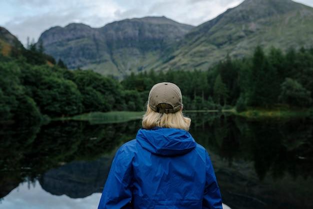 高地の川沿いに立っている人
