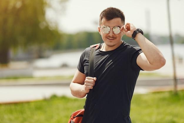 水辺に立っている男。スポーツ服を着た男。バックパックと夏の公園の男性