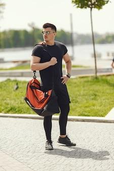 Uomo in piedi vicino all'acqua. ragazzo in abiti sportivi. maschio in un parco estivo con zaino
