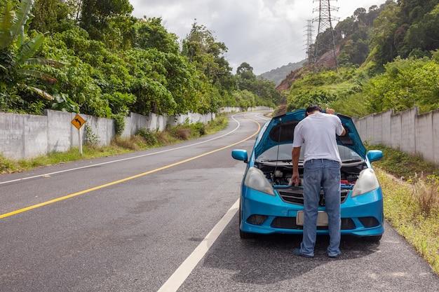 Человек, стоящий проверить машину аварии двигателя на дороге с автомобилем неисправности двигателя посреди дороги.