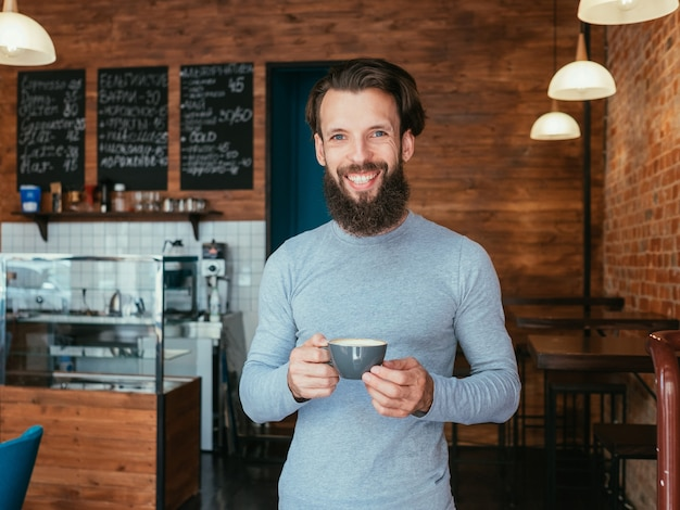 Man standing in coffee shop holding cup of cappuccino