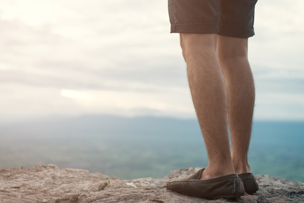 Man standing on edge of a cliff mountain top , travel concept.