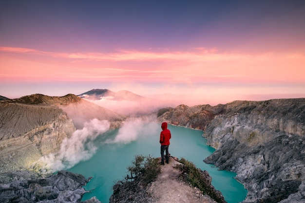 Man standing on edge of crater with colorful sky at morning