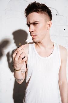 Uomo che sta sul pavimento con la posa della sigaretta