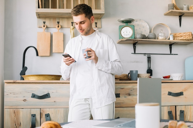 Man standing in front of kitchen counter using mobile phone holding coffee cup