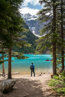 A man standing in front of moraine lake