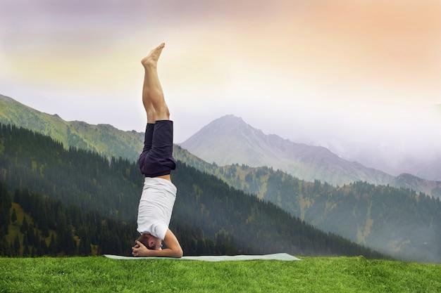 Man standing on her head doing yoga in himalayan mountain.