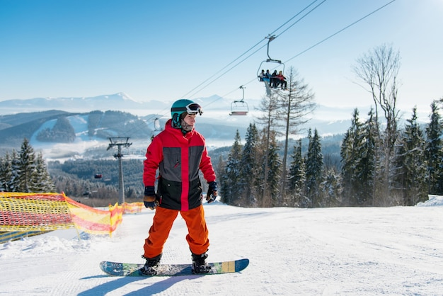 Man standing on his snowboard on a ski slope at winter resort