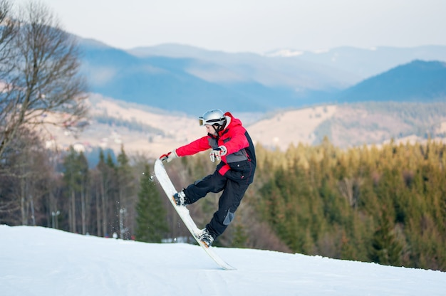 Man standing on his snowboard and taking his for the edge