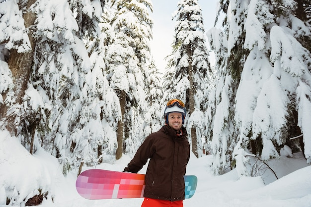 Man standing and holding a snowboard