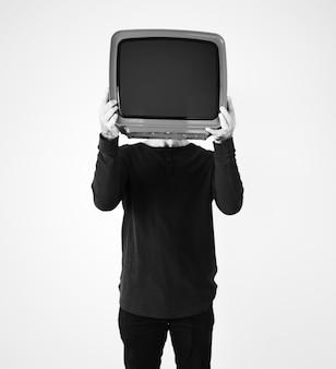 Uomo in piedi e con in mano una tv